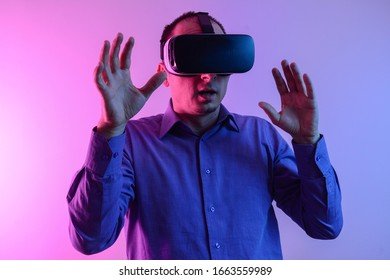 Front view of  man with glasses of virtual reality. Future technology concept. Modern imaging technology.  Isolated on neon light background. VR headset.