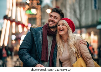 Front view of a man with his arm around his girlfriend outside. The couple are outside on a city street . There is a fair groung ride in the background.
