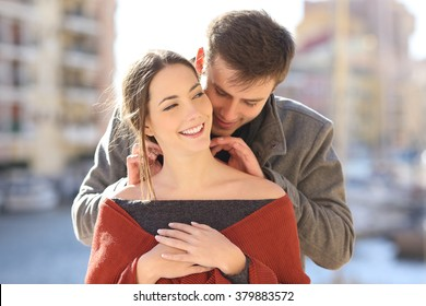 Front view of a man putting a blank necklace jewel to his girlfriend in the street of a romantic place. Jewelry model concept.