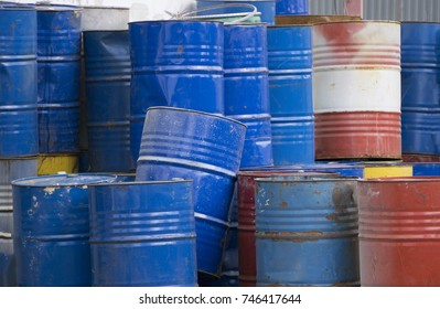 Front view of many rusty iron barrels.