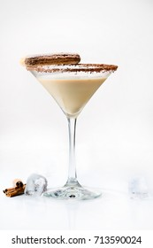 Front view of martini glass with tasty chocolate martini cocktail made from chocolate, cream and vodka, decorated with cinnamon sticks on light background