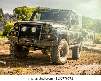 front view of massive 4x4 off-road car on the dirty ground panorama in mountains