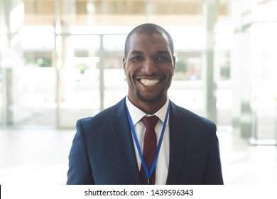 Front view of mature African-american male standing in empty conference room, smiling at camera