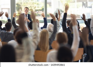 Front view of mature Caucasian businesswoman doing speech and answering questions in conference room