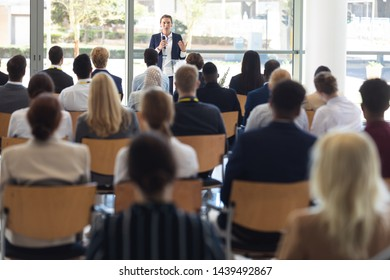 Front view of mature Caucasian businesswoman doing speech in conference room