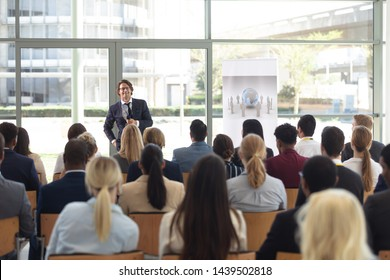 Front view of mature Caucasian male executive doing speech in conference room