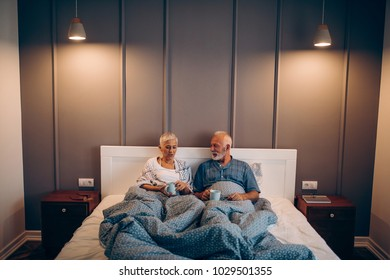 Front view of a mature couple having coffee in bed