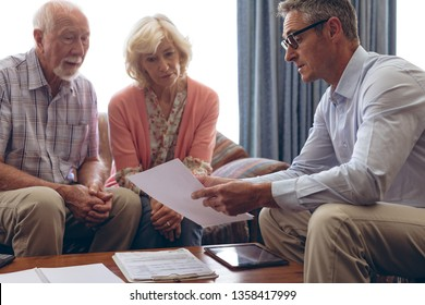 Front view of matured Caucasian male physician interacting and showing medical papers to senior couple at retirement home