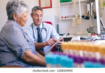 Front view of matured male doctor showing medical report to the senior female patient at clinic at retirement home