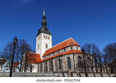 Front view of the medieval former St Nicholas Church, in Tallinn, Estonia, dedicated to Saint Nicholas, on blue cloudy sky background.