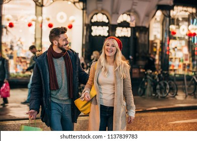 Front view of a Mid adult couple walking around a city street after christmas shopping.