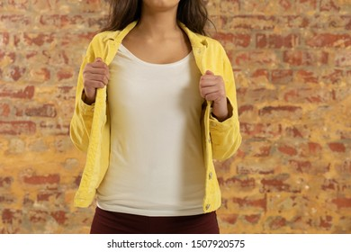 Front view mid section of a young Caucasian woman wearing casual street fashion clothes standing against a brick wall and holding her jacket