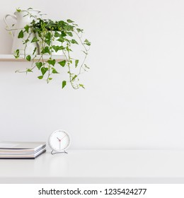 Front view of minimal desk with clock, books and ivy plant on a bookshelf against white wall. Copy space for product display montage.