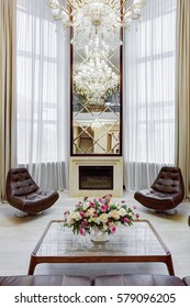 Front view of mirror over fireplace, glasses table, two leather armchairs around. Interior in brown, beige colors. Room with big windows, and flower on table.