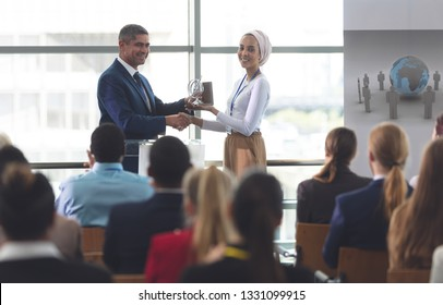 Front view of mixed race businesswoman receiving award from mixed race businessman in front of business professionals sitting at a business seminar in office building