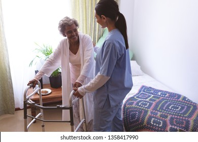 Front view of mixed race female nurse helping senior African American female patient to stand with walker at nursing home