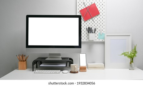 Front view of mock up computer with blank screen, smart phone and office supplies on white desk at home office interior.