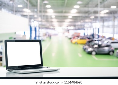 Front view of Mockup with blank screen laptop with blurred car showroom background.