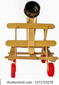a front view of a model catapult made out of ice lolly sticks and plastic tops isolated on a white background