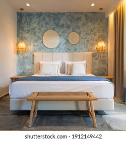 Front view of modern bedroom interior in nautical marine style with blue decorative stucco wall, wicker furniture, ceiling wooden lamps, white soft bed - Shutterstock ID 1912149442