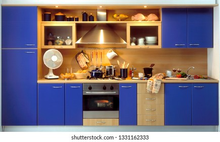 front view of a modern blue kitchen with pots and accessories