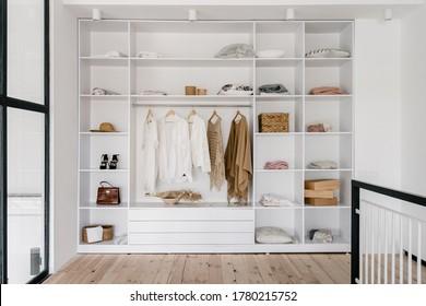Vorderansicht des modernen und großen Schränken im Ankleideraum mit modischen Frauenkleidung, Schuhen und Taschen