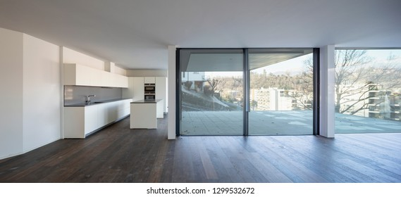 Front view of modern white kitchen with large windows and city view. Nobody inside