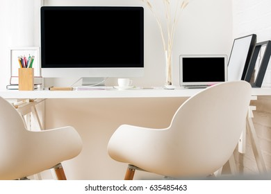 Front view of modern workplace with empty computer, laptop, chairs, supplies and other items. Mock up