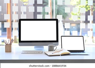 Front view of modern workstation with blank screen computer and laptop on white table.