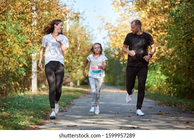 Front view of mother, father and daughter wearing sportswear are jogging in autumn park alley, active family, warm and sunny weather