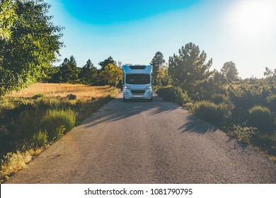 Front view of a motor home on a mountain path on a sunny day. Copy space area available