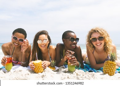 front view of multi ethnic women lying at beach while having pineapple juice on a sunny day