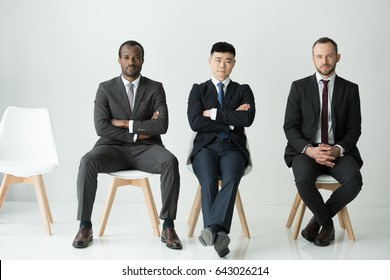 front view of multiethnic businessmen sitting on chairs isolated on white, multicultural business team concept