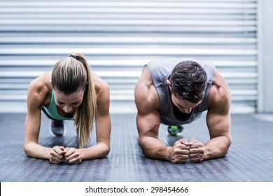 Front view of a muscular couple doing planking exercises