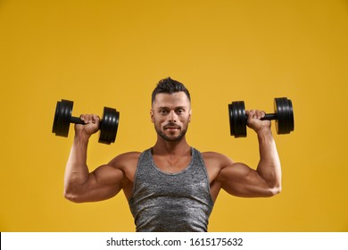 Front view of muscular young man doing exercise for biceps. Athletic guy in sport tank top lifting heavy weights. Isolated on yellow studio background. Concept of bodybuilding and strength training.
