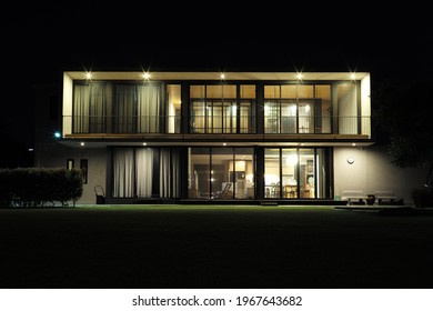 Front view of new house in modern style with lighting at dark night