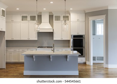 Front view of a newly designed kitchen with a center island inside a model home