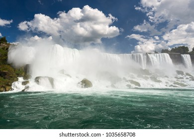 Front view of Niagara Falls with blue sky and white clouds.
