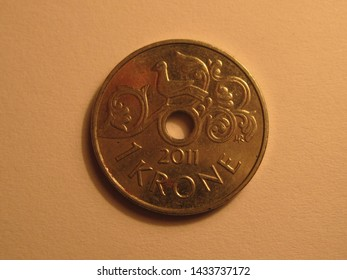 Front view of Norwegian coin. 1 krone from Norway. Great for numismatic collection. Shiny coin from Norway isolated on yellow surface of paper.