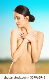 Front view of nude woman crossing her arms on chest.