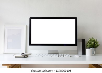 Front view office table desk. Workspace with blank computer screen, keyboard, mouse, booklets, pen, white picture frame , plant mockup, cup, books and white background