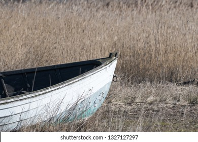 Front view of an old abandoned wooden fishing boat in the reeds