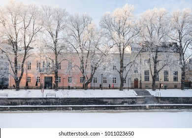 Front view of old colorful building in winter with beautiful frost covered trees on front in Turku, Finland
