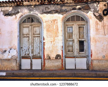 """Front view of an old, dilapidated and rundown old town house in """"San Sebastian""""on """"La Gomera"""" (Canary Island). crumbling plaster and two arched entrance doors with dilapidated formerly white wood."""