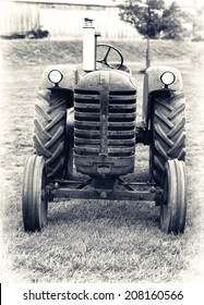A front view of an old farm tractor sitting in a field.  Lightly toned Black and White for an aged vintage look.