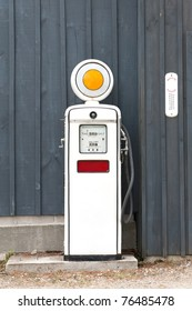A front view of an old fashioned gasoline pump from the 1960's with 42 1/2 cents per gallon on the meter against a blue board and batten background.