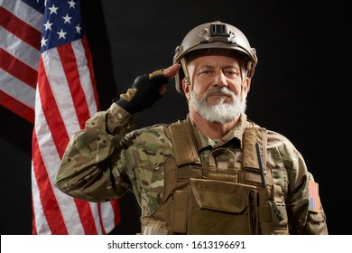 Front view of old military officer saluting and looking at camera. Portrait of bearded american veteran in uniform and helmet posing on black background with flag. Concept of military, army.
