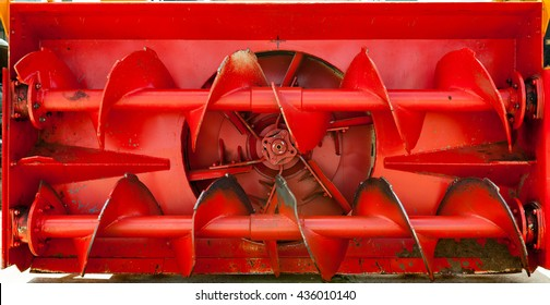 Front view of old red snow plow.