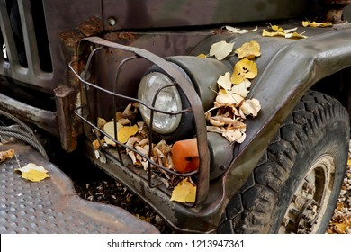 front view of old rusty truck covered with red yellow leaves at autumn, vintage rural scenery