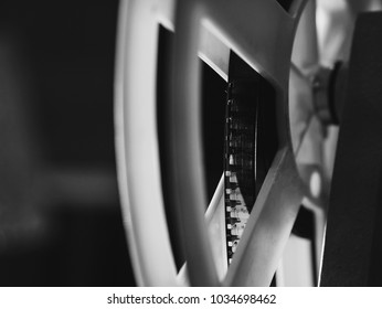 Front view of an old-fashioned antique Super 8mm film projector, projecting a beam of light in a dark room next to a stack of unraveled film reels. Black and white